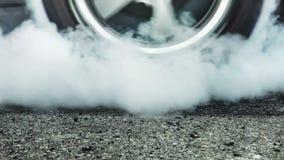 Arrastre los neumáticos de la quemadura del coche de competición en la línea del comienzo almacen de metraje de vídeo