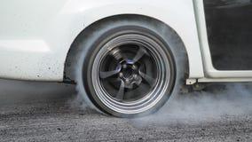 Arrastre los neumáticos de la quemadura del coche de competición en la línea del comienzo metrajes