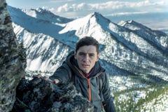 Arrastre turístico del hombre en rocas al top en el fondo de montañas nevosas Logro de la motivación y de la meta fotos de archivo libres de regalías