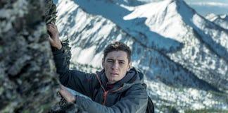 Arrastre turístico del hombre en rocas al top en el fondo de montañas nevosas Logro de la motivación y de la meta fotografía de archivo libre de regalías