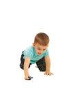 Arrastre y juego del muchacho con el pequeño coche del juguete Foto de archivo