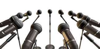 Microphones and Stands Array. An array of black plastic and foam microphones on stands facing inwards on an isolated background royalty free stock images