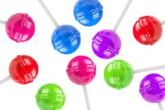 An array of colored lollipops. An array of spherical lollipops on sticks made  in various colors including  orange, red, green, purple and blue, white background Royalty Free Stock Photos