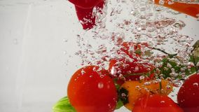 Array fresh vegetables, cucumber, pepper and tomatoes dropping in water, slow motion close-up. On a white background. Full HD Video stock footage