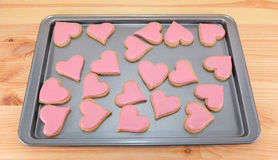 Array of heart-shaped cookies with pink frosting Royalty Free Stock Images