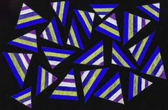 Multicolored triangles. An array of purple, white, green (pale yellow)  and blue striped triangles surrounded by a black background Royalty Free Stock Photo