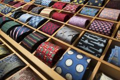 Array of retailer ties on display in square compartments. Ties rolled up in square sections Royalty Free Stock Photo