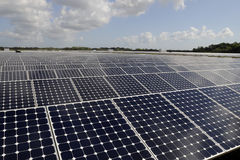 Array of solar panels. Array or grid of solar panels outdoors under cloudscape stock photo