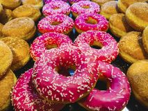 Array of sugar sprinkled doughnut and pink color for background royalty free stock photos