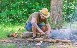 Arregle las ramitas de maderas o los palillos de madera que se colocan como una pirámide y coloque las hojas debajo Cómo construi imagenes de archivo