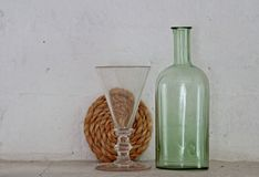 Arreglo con el vidrio claro y la botella verde vieja Fotos de archivo
