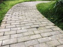 Arreglo concreto del sendero por la curva en el jardín imágenes de archivo libres de regalías