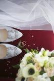 Arreglo de la boda, anillos, zapatos, velos y ramo nupcial Foto de archivo