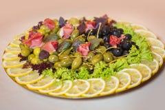 Arreglo de la comida en la placa con las salmueras, aceitunas, verdes, tocino, limón Imagenes de archivo