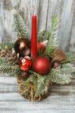 Arreglo de la Feliz Navidad en rama imperecedera del fondo de madera con los globos rojos, los pinecones, y la vela roja Fotografía de archivo libre de regalías