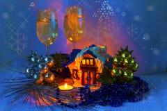 Arreglo de la Navidad con la casa de cerámica con las velas y dos de Foto de archivo