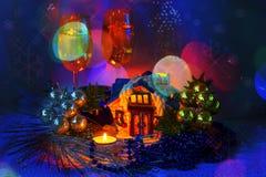 Arreglo de la Navidad con la casa de cerámica con las velas y dos de Imágenes de archivo libres de regalías