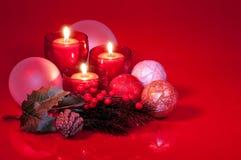 Arreglo de la Navidad de velas y de ornamentos rojos Foto de archivo libre de regalías