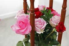 Arreglo de las rosas rosadas y rojas con madera Foto de archivo