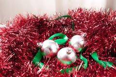 Arreglo de los ornamentos y de la cinta de plata de la Navidad en la guirnalda Foto de archivo