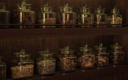 Arreglo de los productos alimenticios secos en estantes de madera oscuros Imagen de archivo