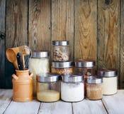 Arreglo de los productos alimenticios y de los utensilios secos de la cocina en la cocina Imágenes de archivo libres de regalías