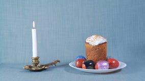 Arreglo de Pascua, Pascua en la placa blanca con los huevos teñidos, vela blanca ardiente próxima almacen de video