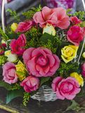 Arreglo de rosas en una cesta colocada en parada del mercado fotografía de archivo