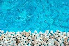Arreglo decorativo de las cáscaras del mar en un fondo azul Imagenes de archivo
