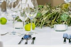 Arreglo en la tabla en verde con los vidrios para el vino Fotos de archivo