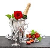 Arreglo festivo con champán, la rosa del rojo y las fresas foto de archivo