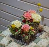 Arreglo floral de rosas en cesta Fotos de archivo