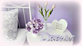 Arreglo interior en la mesita de noche: hortensia, tulipanes y letras en tonos púrpuras Imagenes de archivo
