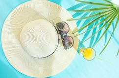 Arreglo plano de la endecha del vidrio alto de las gafas de sol del sombrero de paja con la hoja de palma fresca del zumo de frut imagen de archivo