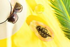 Arreglo plano de la endecha de Straw Hat Sunglasses Tall Glass con el fondo fresco de Juice Papaya Palm Leaf Yellow de la fruta t imagen de archivo libre de regalías