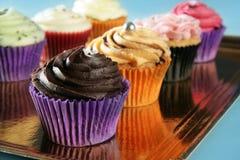 Arreglo poner crema colorido del mollete de las magdalenas Imagen de archivo libre de regalías