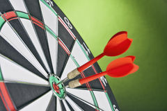 Arremessa as setas que batem o centro do alvo em um fundo verde Fotografia de Stock Royalty Free