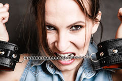 Arrest. Criminal woman prisoner biting handcuffs Stock Photos