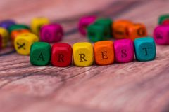 Word created with colored wooden cubes on desk. Arrest - word created with colored wooden cubes on desk Royalty Free Stock Image