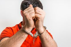Arrestant in handcuffs verborgen zijn gezicht Stock Foto