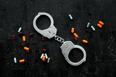 Arrestatie voor onwettig aankoop, bezits en verkoopdrugsconcept Drugs als pillen dichtbij handcuff op zwarte bovenkant als achter stock foto's