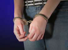 Arrested. Woman in handcuffs with blue background Stock Image