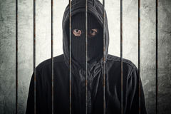 Arrested burglar behind bars Royalty Free Stock Image