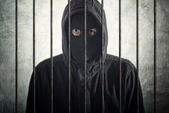 Arrested burglar behind bars royalty free stock image