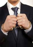 Arrested businessman. Arrested business man handcuffed hands. Close-up Royalty Free Stock Images