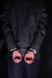 Arrested businessman handcuffed hands at the back. Close-up. Arrested businessman handcuffed hands at the back Royalty Free Stock Photo