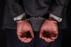 Arrested businessman handcuffed hands at the back. Close-up. Arrested businessman handcuffed hands at the back Royalty Free Stock Photography