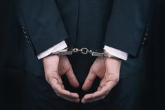 Arrested businessman in handcuffs with hands behind back stock images