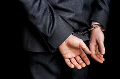Arrested businessman in handcuffs with hands behind back. Isolated on black background Royalty Free Stock Image