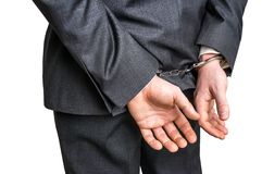 Arrested businessman in handcuffs with hands behind back. Isolated on white background Stock Images